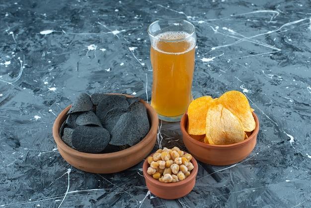 Diversos petiscos em taças e um copo de cerveja, no fundo azul.