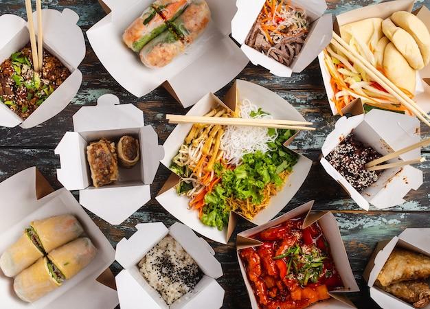 Diversos pratos chineses em caixas de entrega de papel: frango agridoce, dim sum, rolinhos primavera, macarrão, salada, arroz, pãezinhos no vapor, molhos. restaurante asiático take away, vista de cima