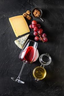 Diversos queijos da europa, uvas, vinho e nozes sobre fundo preto, copie o espaço. vista do topo.