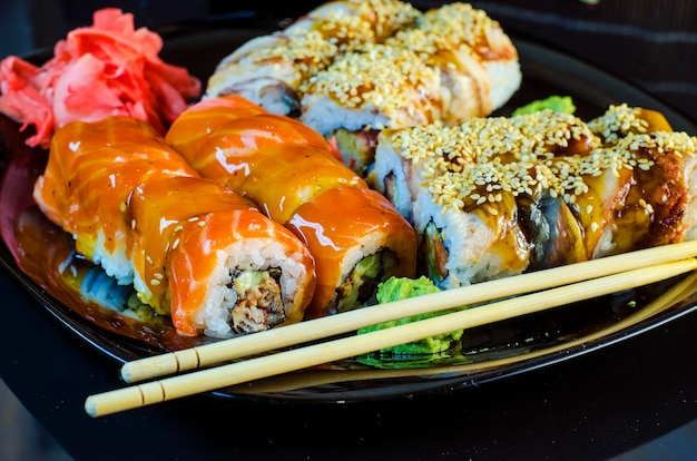 Diversos rolos de sushi em uma tigela preta com pauzinhos