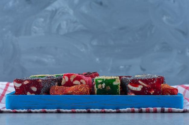 Diversos sabores de delícia turca em uma placa de madeira, no pano de prato, na mesa de mármore.