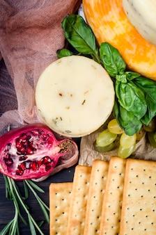 Diversos tipos de queijo caseiro com vegetais, frutas, biscoitos e nozes na mesa. produtos lácteos frescos, alimentos orgânicos saudáveis. aperitivo delicioso.