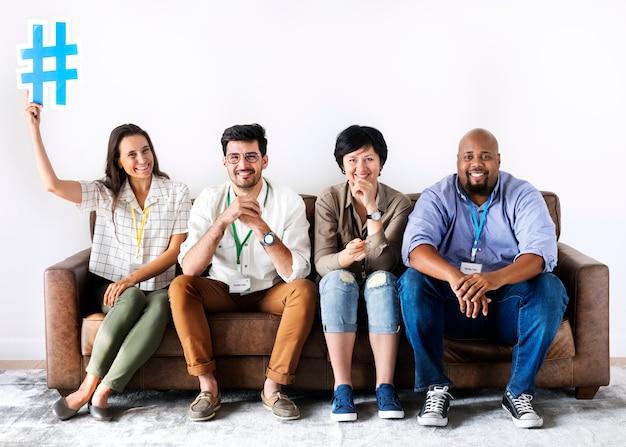 Diversos trabalhadores sentados juntos mulher segurando o ícone de hashtag