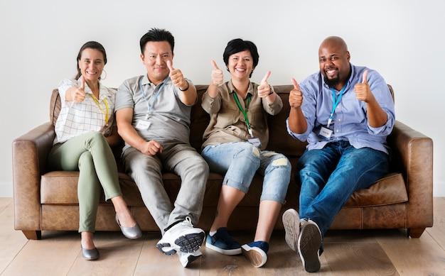 Diversos trabalhadores sentados juntos no sofá sorrindo