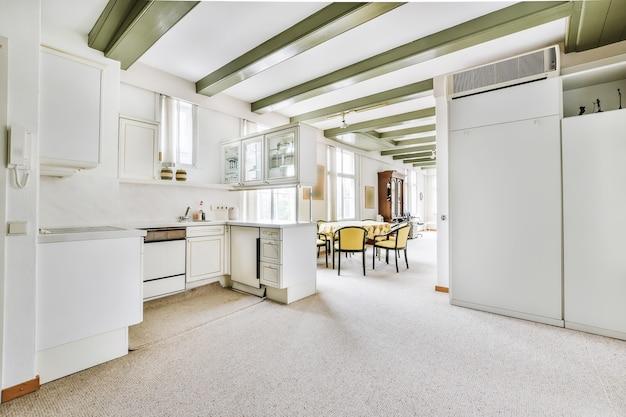 Diversos utensílios de cozinha e eletrodomésticos colocados em balcões com armários brancos acima na cozinha contemporânea em casa