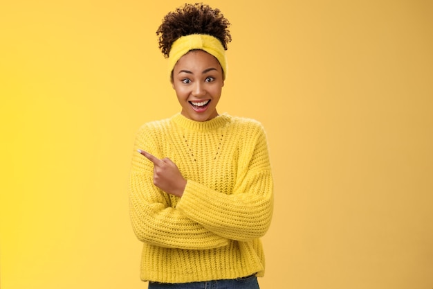 Divertida carismática sorridente linda garota negra no suéter com bandana arregalar os olhos caírem da mandíbula espantado ouvir sobre um novo lugar interessante e incrível amigo falando em pé fundo amarelo apontando para a esquerda espantado.