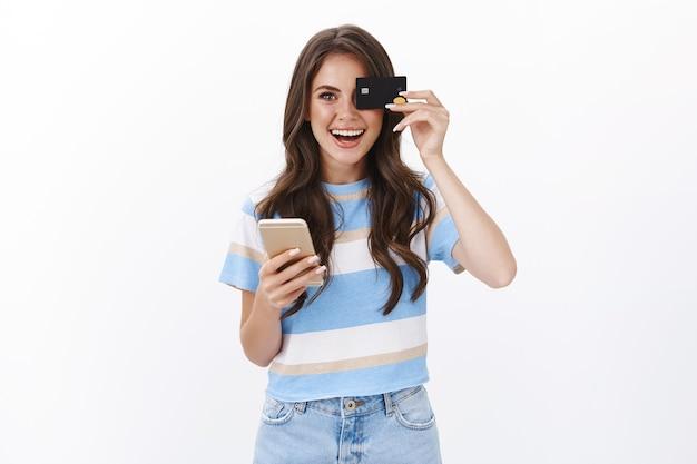 Divertida garota moderna europeia divertida gosta de encomendar produtos online, reservar um voo para smartphone, segurar o telefone celular e o cartão de crédito perto dos olhos, sorrindo alegremente, comprar na loja da internet, parede branca