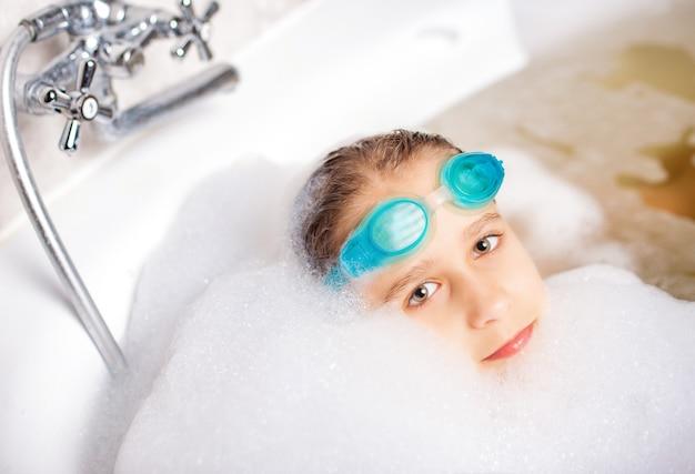 Divertida menina caucasiana positiva usando óculos de natação e brinca na banheira com espuma enquanto espera para relaxar à beira-mar