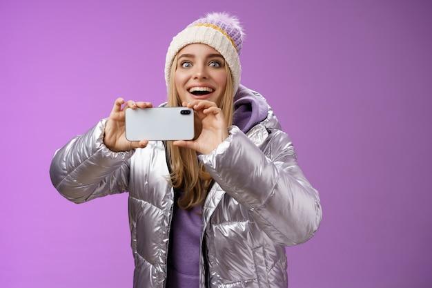 Divertida mulher fascinada na cabeça de jaqueta prateada sorrindo surpreso animado olhando para a frente segurando smartphone gravação de vídeo tirando fotos de câmera de celular de pessoa famosa, fundo roxo.