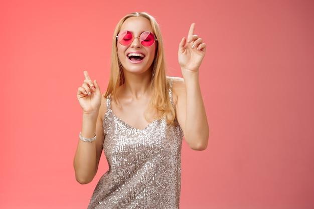 Divertido atraente feliz sorridente mulher dançando boate se divertindo, curtindo ir selvagem festa comemorando aniversário de aniversário usando um vestido estiloso, óculos escuros levantando o dedo indicador sorrindo cantando junto