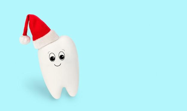 Divertido brinquedo dente branco com chapéu de papai noel vermelho, isolado sobre fundo azul claro. conceito festivo para clínica odontológica. cartão de inverno médico de natal e ano novo, personagem bonita para cartaz, copie o espaço.