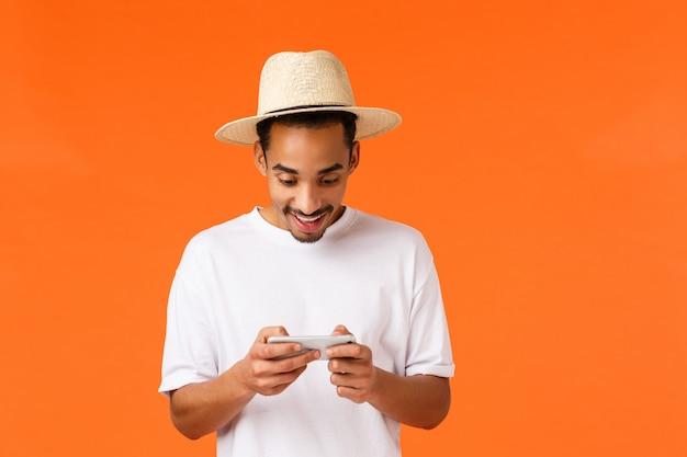 Divertido cara nerd afro-americano jogando jogo de smartphone no aeroporto enquanto aguarda o vôo, segurando o celular horizontalmente entretido, baixe o aplicativo de corrida, toque na tela, queira ganhar, parede laranja
