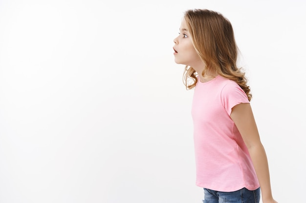 Divertido imaginou curiosa garotinha intrometida com cabelo loiro em pé de perfil, boca aberta fascinada assistir a uma performance incrível e legal, olhar para a esquerda copie o espaço com interesse e alegria, pose para parede branca