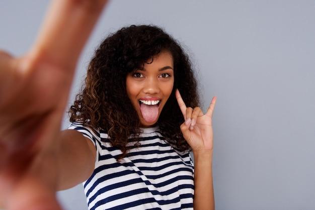 Divertido jovem americana africano tomando selfie com a língua
