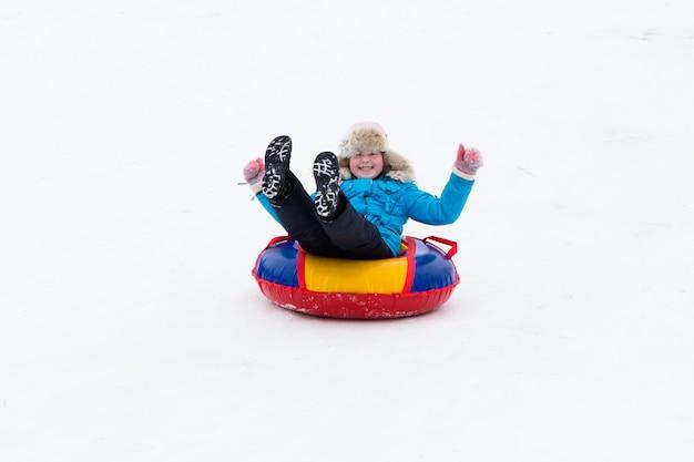Divertimento ativo do inverno - passeio feliz da menina da colina da neve nos tubos