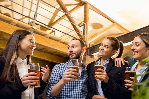 Divertindo-se colegas de trabalho felizes comemorando evento corporativo após um dia tenso de trabalho