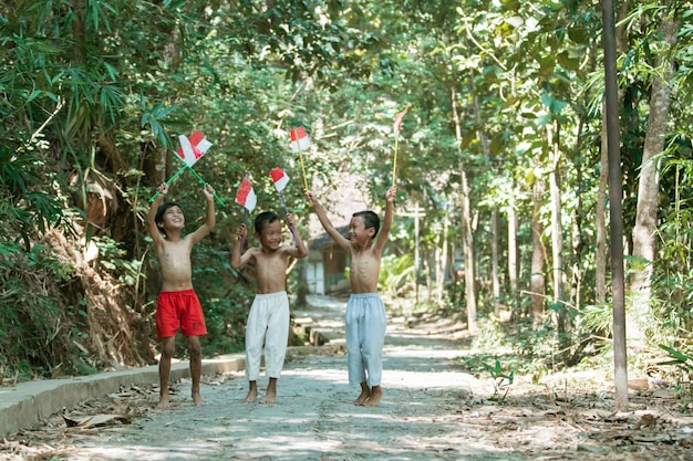 Divertindo-se com três meninos em pé sem roupa segurando pequena a bandeira vermelha e branca