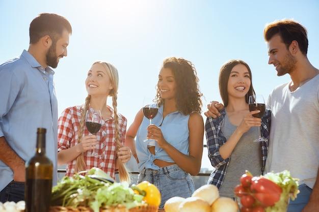 Divertindo-se com um grupo de amigos jovens e felizes sorrindo e bebendo vinho