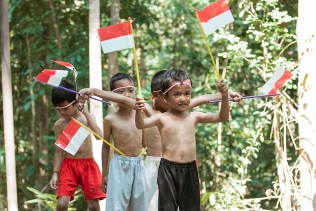 Divertindo-se grupo de crianças em pé sem roupas segurando uma pequena bandeira vermelha e branca e erguendo a bandeira