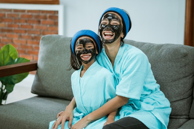 Divertindo-se mãe e filha usando máscaras faciais de argila juntas enquanto relaxam no sofá
