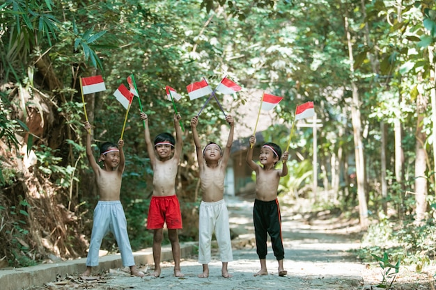 Divertindo-se um grupo de crianças em pé sem roupas segurando uma pequena bandeira vermelha e branca