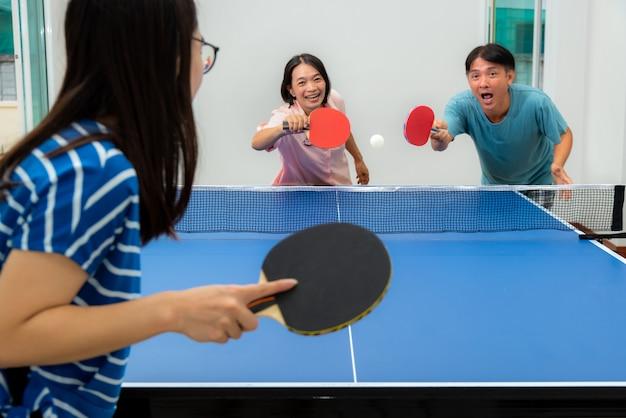 Divirta-se jogando tênis de mesa ou pingue-pongue coberto com lazer e competindo em jogos esportivos em casa. pai, mãe e filha de família asiática desfrutam de exercícios de recreação em casa na tailândia
