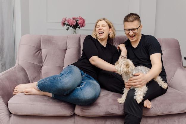 Divirta-se jovem casal na sala de estar no sofá rosa junto com seu animal de estimação. descanse e relaxe.