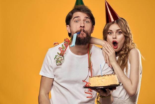 Divirta-se um homem e uma mulher no aniversário com um bolo e uma vela em bonés festivos