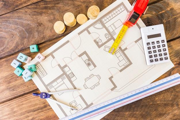 Divisor, régua, blocos de matemática, calculadora, moedas empilhadas e blueprint na mesa de madeira