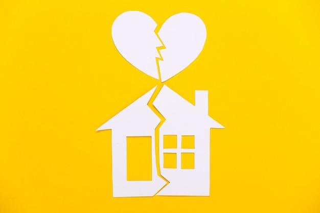 Divórcio, conceito de divisão de propriedade. casa de papel dividida e coração partido em amarelo