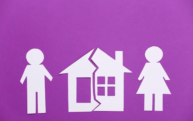 Divórcio. divisão de propriedade. homem e mulher de papel divididos, casa destruída em roxo