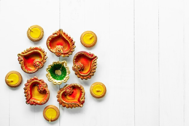 Diwali feliz - as lâmpadas de clay diya acenderam-se durante dipavali, celebração hindu do festival de luzes. diya de lâmpada de óleo tradicional colorido na mesa de madeira branca