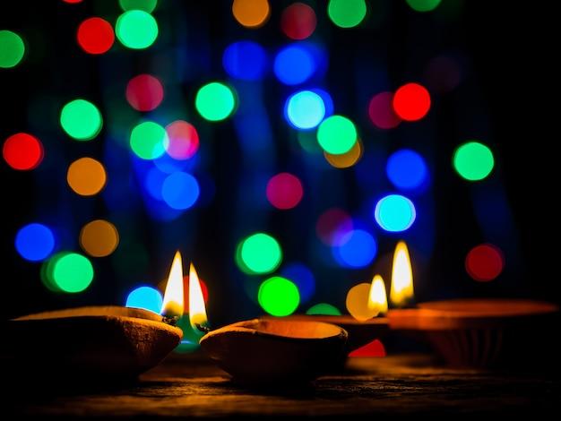 Diwali feliz - as lâmpadas de diya iluminaram-se com fundo do bokeh durante a celebração do diwali.