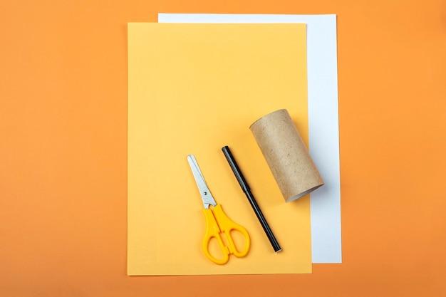 Diy e criatividade infantil. instruções passo a passo: como fazer o símbolo de 2022 do tigre com um tubo de papel higiênico. ferramentas de prerpration da etapa 1: tesoura, papel laranja. artesanato de ano novo e natal de crianças.
