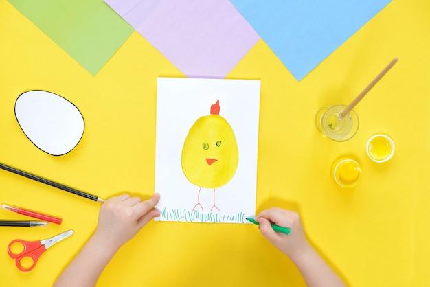 Diy e criatividade infantil. instruções passo a passo crie um cartão de páscoa com frango. desenhe frango capim com uma caneta de feltro verde.