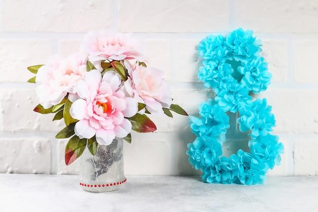 Diy oito fez papelão decorado flor artificial feita de tecido azul guardanapo de papel branco fundo.