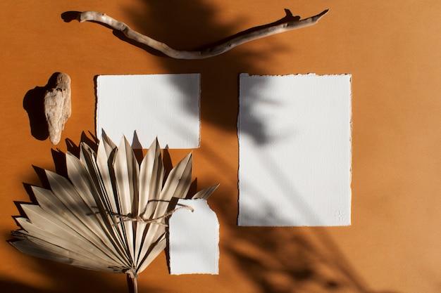 Diy papel em branco branco poster cartões de convite de casamento conjunto com folha de palmeira seca na mesa de terracota texturizada. elegante modelo moderno para identidade de marca. vista plana, vista superior