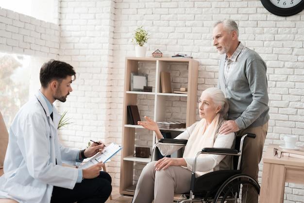 Diz resultados de exame de paciente idoso em cadeira de rodas