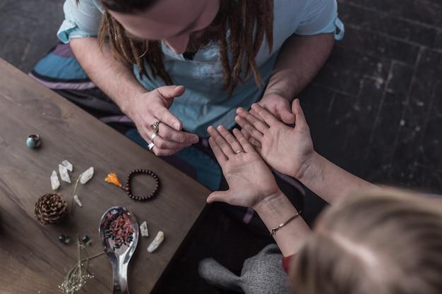Dizendo o destino. vista superior das palmas sendo mostradas ao quiromante durante uma sessão com ele