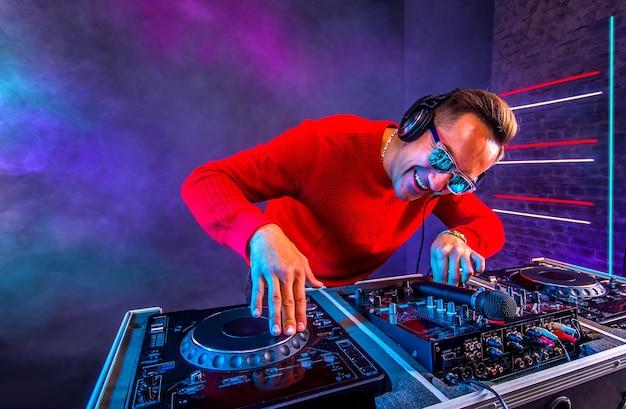 Dj alegre mixando faixas em uma toca-discos na boate