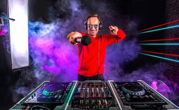 Dj atraente com microfone tocando no toca-discos na boate. clube, vida noturna.