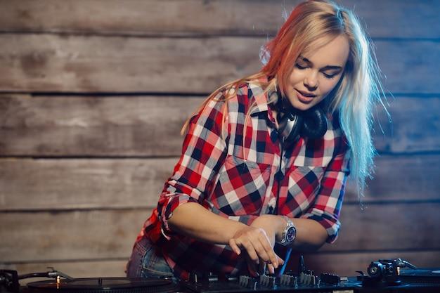 Dj bonito mulher se divertindo tocando música na festa do clube
