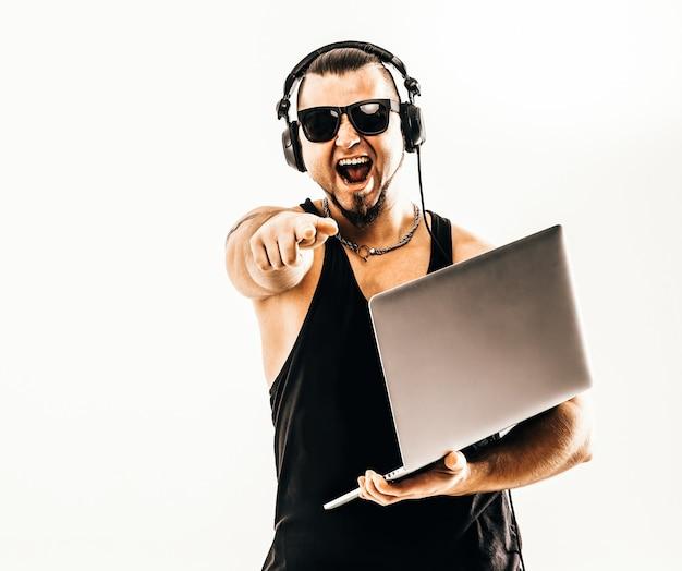 Dj carismático - rapper em fones de ouvido e com um laptop .foto em um fundo branco e tem um espaço vazio para seu texto