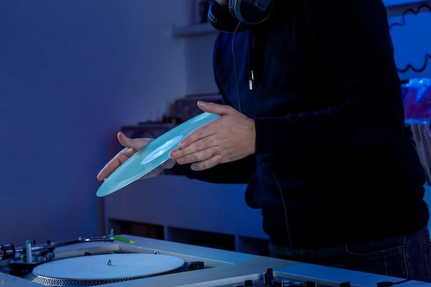Dj colocando un disco de vinilo em su tocadiscos mientras mezcla msica em uma tienda de discotecas