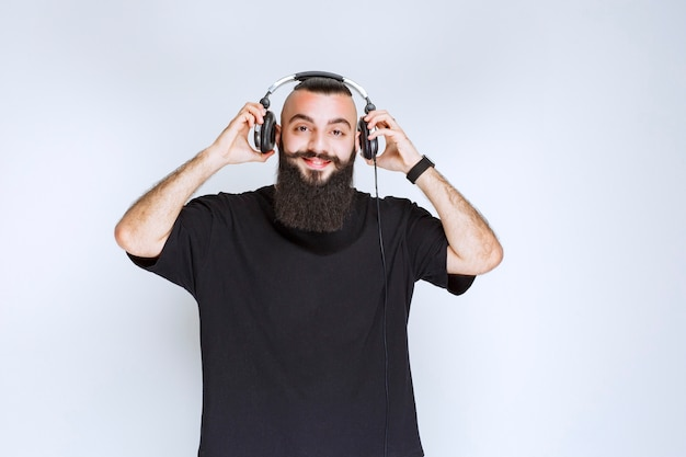 Dj com barba tirando fones de ouvido para ouvir a voz externa.
