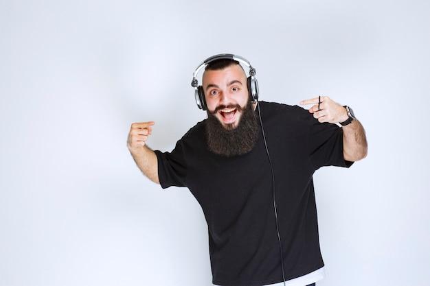 Dj com barba usando fones de ouvido, dançando e se sentindo ativo.