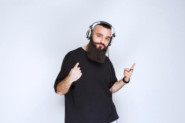 Dj com barba usando fones de ouvido e apontando para cima.