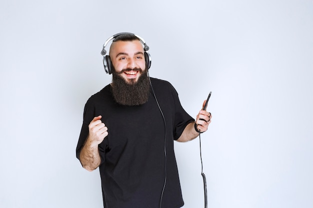 Dj com barba usando fones de ouvido e curtindo a lista de reprodução em seu telefone.