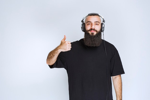 Dj com barba usando fones de ouvido e mostrando sinal positivo com a mão.