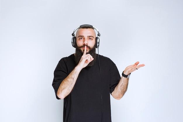 Dj com barba usando fones de ouvido e pedindo silêncio.